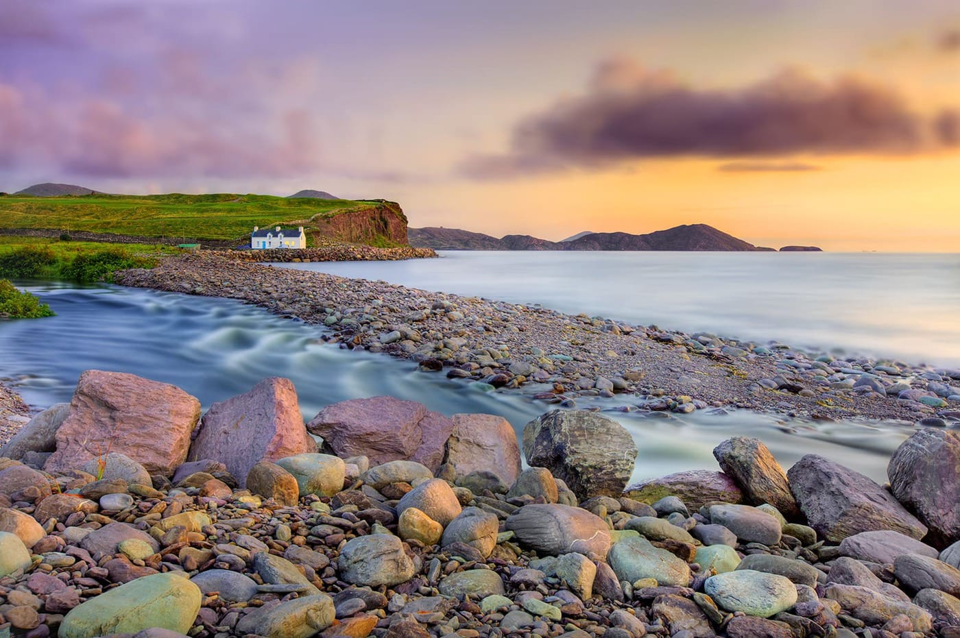 Waterville is a town in County Kerry, Ireland on the Iverah Peninsula. The town is sited on a narrow isthmus, with lough Currane on the est side and Ballinskelligs Bay on the west. View on Cottage and Skellig Bay Golfcourse during sunset